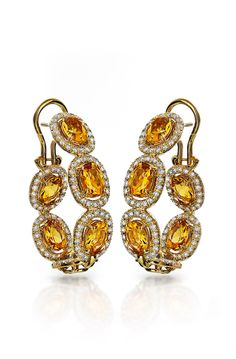 "A spectacular display of light and shine, these amazing Haute Vault citrine earrings will be a dazzling compliment for any special event. Our 18K yellow gold in-out design hoop style earrings feature citrines surrounded by diamonds.   Pair with diamond stacked bangles and a coordinating citrine ring and your look will reign in the arena of glamour. Measures 1 1/4"" long and 7/8"" wide"