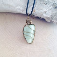 """Amazonite Wire Wrapped Crystal Necklace. Made with antique brass wire on a leather necklace. Choose leather color and length. Popular choices are Choker (16""""), Pendant (18""""), Matinee (22""""), Opera (30""""), and Rope (40""""). Pendant is shown both with Black and Natural/Tan leather.  Wear Amazonite to..."""