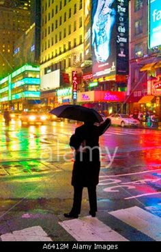 Man Hailing Taxi With Umbrella In The Rain At Night, New York City Times Square, New York, USA    © JG Photography / Alamy