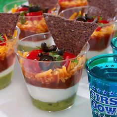 Mini chip-and-dips score a major snackdown! Just layer guac, sour cream & salsa in a plastic shot glass with a sprinkle of cheese, tomatoes, olives & green onions!