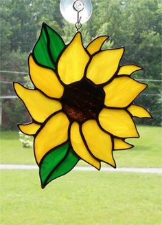Stained Glass Sunflower Suncatcher - Handcrafted in the USA. Built in the foil and solder method. Measuring approx. 8.5 x 7 inches. This Sunflower was built using a semi-transparent sunshine yellow with white wisp for the flower petals. The center of the flower is a granite textured brown with wisp of caramel. The leaves are a green with wisp of white. This piece has had black patina to enhance glass colors. The hanging point is a twisted wire soldered securely for safe display. Comes ...