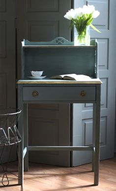 a beautiful little writing desk painted by libby moore in duck egg blue over chateau grey, topped with clear and dark wax.  she used gold leaf on the edges of the desk, and gilding wax on the pulls.