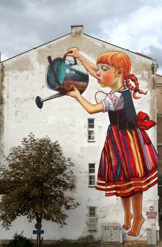 Last week in Poland, Natalia Rak painted a new mural for the Folk on the Street 2013 event. Playing with ideas of scale, the clever piece features a girl watering a small plant or tree depending on your perspective and can be found on the side of the Institute of Chemistry building at the University of Bialystok. Take a closer look at the mural in the photos below…