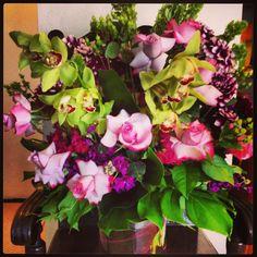 XL flower arrangement in purple & greens featuring cymbidium orchids, roses , dahlias & others.