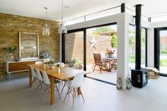 Broadgates Road - Granit Architects. Open dining space, glass pendant lights, exposed brick wall, wood burner, garden dining, eames chairs, tiled flooring. Rear extension in Wandsworth, South West London.