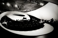 Tensile fabric structure weaving through architecture.
