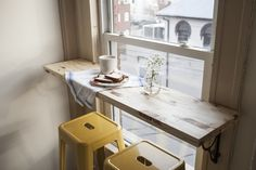 a simple breakfast bar created with a shelf and 2 stools. Perfect for small city apartments.