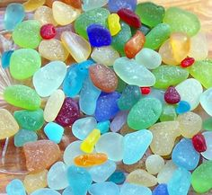 "Sea glass tinies are these little bits of glass less than the size of a pea. Many times you can find the best colors getting really ""down to earth,"" or ""down to sand"" in this case; searching on your hands and knees along the tide line of the beach."