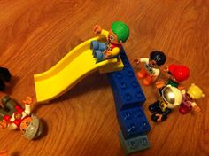 Playing going down the slide  with Lego Duplo people.