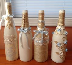 Amber, here are 4 of your bottles.  The one on the left still needs something.  Have 3 more to do. Stone fleck spray paint, jute, lace, ribbons, silk spray painted flowers to match, burlap, and pearls from some old jewelry. Bottles by Donna Ravellette