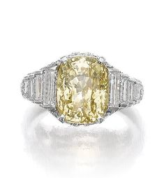 YELLOW SAPPHIRE AND DIAMOND RING, BULGARI, 1970s. Set with a cushion-shaped yellow sapphire weighing 9.97 carats, brilliant-cut and baguette diamonds, size 52, signed Bulgari.