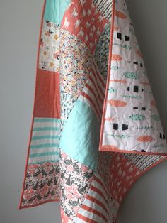 This adorable baby girl quilt is completed and ready to ship to you! It features a beautiful, soothing palette of coral, muted aqua, grey and