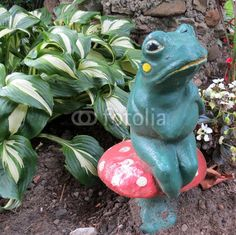 Old, ceramic frog sits on a toadstool in the garden.