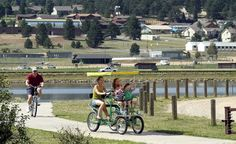 Guests riding the path along Lake Estes in Estes Park, CO. (From: PHOTOS: America's Coolest Small Towns 2014) #budgettravel #travel