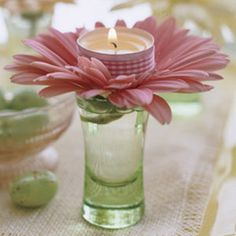 All you need are candles, ribbon, gerbera daisies, cordial glasses, and double-stick tape. Affix a length of ribbon around the metal rim of the votive. Snip off almost the entire stem of the flower, splay out the petals, and insert into the glass. Top each daisy with a lit candle. For a twinkling effect, place a glass at each setting.