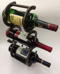 Wine rack, from used horse shoes, holds 3 wine bottles or bottles of like size. Finished with a brown wrinkle finish. From ScrapIronDesigns on etsy