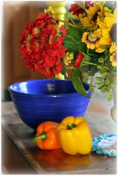 Such vivid color in flowers and vegetables...then there is that blue bowl.