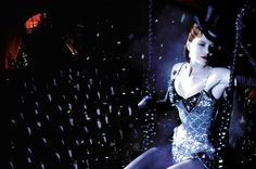 """The Movies' Best-Loved Costumes   Nicole Kidman as Satine in """"Moulin Rouge!"""" (2001)  Star of the Moulin Rouge night club, the dancer-prostitute Satine lounges on a swing above the crowd. Her circus-aerialist bustier is fronted with a bow-tie bodice; a top hat frames her pale face. Production and costume designer Catherine Martin, the wife of director Baz Luhrmann, gorgeously realized this dream of love and lust set to pop music."""