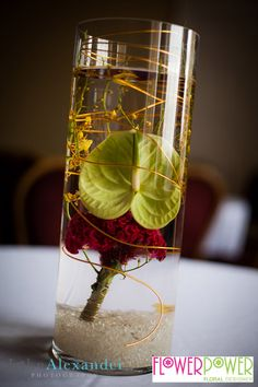 One of the glass vase designs flower Power created - this one containing red celosia and a green anthurium.