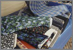 Streekdrachtstoffen op de marktkraam van de heer Booy uit Zwartsluis, gefotografeerd op de markt in Staphorst. Op het blauwe zeil van de kraam zien we verschillende rollen stof. O.a. katoen, wollen mouseline en diverse kunstvezels. De stoffen kunnen worden gebruikt voor kraplappen, schortestukjes en karbiezen (tassen). De verschillende stoffen zijn te gebruiken voor zware rouw, lichte rouw en niet-rouw. 2002 #Overijssel #Staphorst