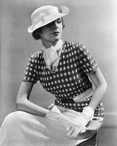 1930's Fashion - Model wearing a checked blouse, white skirt and scarf made of a new tricolour yarn called Cloisonne; worn with Norman Blum's perforated white doeskin gloves and white Panama hat - January 1935 - Vogue - Photo by Lusha Nelson - @~ Mlle