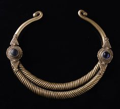 Afghanistan   Neckring; brass, open form with scrolled endings, forming two spiral-shaped rings to the front, the intersection decorated with rosettes set with blue glass stones.  In pre-islamic Kafiristan only men and women of high ranks were allowed to wear such rings   Est.  260 - 400 €