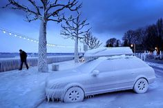 A man walks past an ice-covered car on the frozen waterside promenade at Lake Geneva, Switzerland. February 2012.