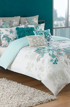 Bedroom: beige walls, off white and teal accents, wood furniture, black metal headboard, white and teal bedding