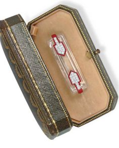 AN ART DECO DIAMOND, ROCK CRYSTAL AND ENAMEL BROOCH, BY CARTIER  Designed as a rock crystal rectangular-shaped open plaque, decorated at the sides with single-cut diamond and red enamel geometric detail, mounted in platinum, circa 1925, in a Cartier green leather case Signed Cartier