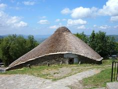 A palloza is a traditional thatched house as found in the in Galicia, Spain. They are circular or oval, and about ten or twenty meters in diameter. These houses are built to withstand severe winter weather. The main structure is stone, and is divided internally into separate areas for the family and their animals, with separate entrances. The roof is conical, made from rye straw on a wooden frame. There is no chimney, the smoke from the kitchen fire seeps out through the thatch.