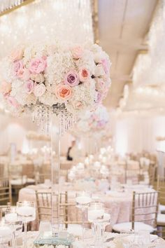 Some tables will have tall crystal stand topped with a ball of white hydrangea, sangria roses, lavender roses and dark magenta spray roses. Surrounded at the base by tall stemmed fluted votives with floating candles in purple water and silver mercury glass votives