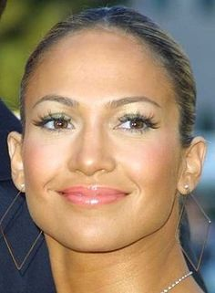 Jennifer Lopez Dazzles in Bright Colorful Makeup: Green/Gold/White Eyeshadow, Eyelash Extensions, Curled Lashes with Three Coats of Mascara, Lined Upper and Lower Lashes, Pink Blush, Shimmer Powder  Highlighter, Glossy Pink Lips.