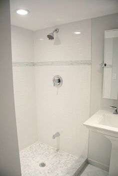 inexpensive subway tile with more expensive carrara on the floor and with an accent strip around the shower