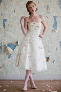 A champagne lace overlay, pearly accents, and sparkling silver centered floral appliques unite with a classic silhouette in white satin to create pure romantic enchantment. Perfected with optional shoulder straps, interior bust cups, and a full skirt.