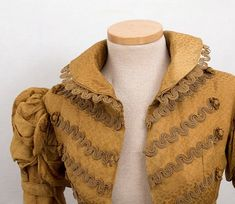The coat was made from gold silk damask woven with a pattern of small dots. The bodice, long sleeves, and skirt back are lined with brown...