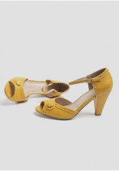 <p><span>Rendered in gorgeous mustard-hued faux leather, these darling retro-inspired heels feature peep-toes with cute button accents. Finished with perforated oxford-style detailing, these charming shoes would look lovely styled with a midi skirt and button-up blouse. By Restricted.