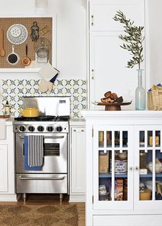 COMPACT KITCHEN  Skinny appliances give this miniature kitchen full-size function. The FiveStar range, with burners spanning the top of the unit, looks hunkier than its 24 inches. Cabinetry panels conceal an 18-inch dishwasher and refrigerator. A framed pegboard provides practical and livable storage.