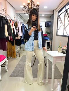 Look calça flare off white e maxi colete jeans.