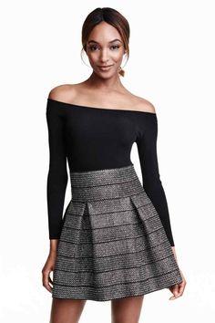 Klokkende rok Rok met structuurdessin: Een klokkende rok van stevig tricot met een structuurdessin en stolpplooien. De rok heeft een zichtbare ritssluiting achteraan. Ongevoerd.