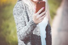 Young Woman Holding Her iPhone in Leather Case Free Stock Photo Download   picjumbo