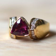 Estate 14 karat yellow gold 2.30 carat rhodolite garnet ring with diamonds. This ring features a trillion cut rhodolite garnet at 2.30 carats and 18 full cut diamonds at 0.50 carat total weight VS2-SI1 clarity H-J color. Size 6.5. Appraised at $1,800.