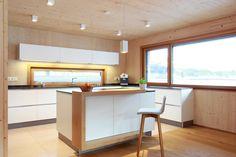 Elegante grifflose Wohnküche mit Kochinsel im modernen Holzhaus. U-förmige Bar, peferkt als Frühstücksplatz.