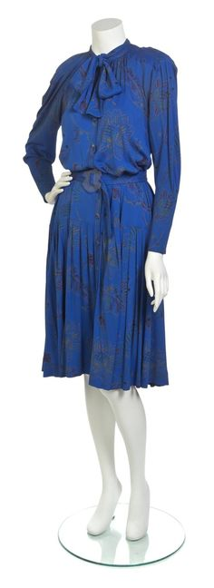 "Jean Muir Blue Print Jersey Dress. ""dolman sleeves, button down front, attached neck tie, drop waist , knife pleated skirt, and and self belt with clear plexi buckle. Labeled Jean Muir London."" Lot# 152--- lot image"