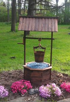 Wishing Well in my own personal garden. I used blue fire glass below the bucket in the well to appear like water glistening in the sun.