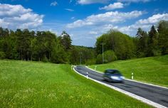 Car driving down Eurpean road in spring (© Ocean/Corbis) ()