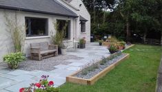 Fabulous blue limestone patio design with flower beds made created with sleepers. #Gardenideas