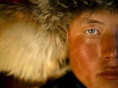 Kazakh Eagle Hunter, Western Mongolia The hunt always begins on horseback, the eagle riding blindfolded on the leather-covered arm of its owner. Fathers and sons, like 17-year-old Sangsai, set out in bitter cold of winter before sunrise to reach promontories where the eagle, blindfold undone, can quickly scan the wide open landscape for prey as the sun rises.