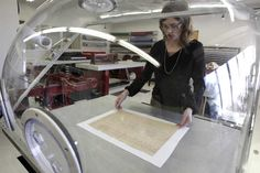 Conservator Sarah Norris places a page on the moveable suction table under the humidity dome.