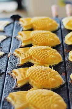 """Taiyaki (たい焼き , literally """"baked sea bream""""?) is a Japanese fish-shaped cake. The most common filling is red bean paste that is made from sweetened azuki beans. Other common fillings may be custard, chocolate, or cheese. Some shops even sell taiyaki with okonomiyaki, gyoza filling, or a sausage inside."""
