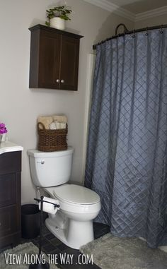 BATHROOM. Curved shower curtain rod and basket for toilet paper.